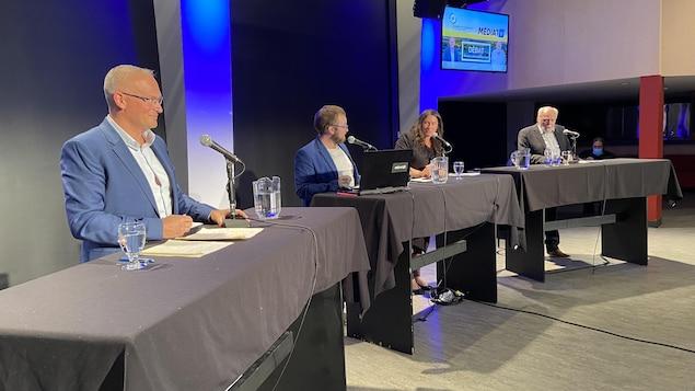 Sébastien D'Astous, François Munger, Annie-Claude Luneau et André Brunet devait un micro lors d'un débat.