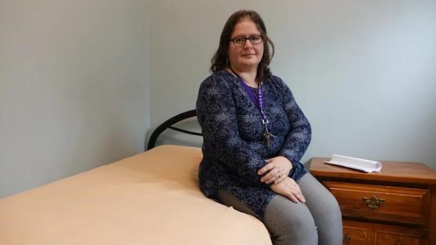 Une femme assise sur un lit.