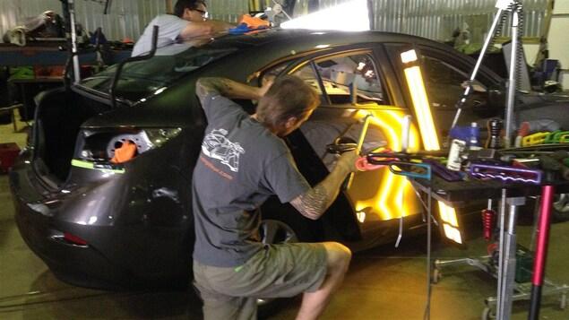 Deux débosseleurs sont en train de réparer la carrosserie d'un véhicule.