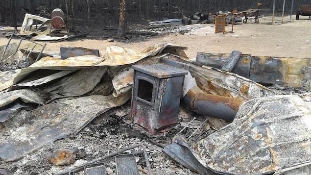 Des objets de métal jonchent le sol après le passage du feu.