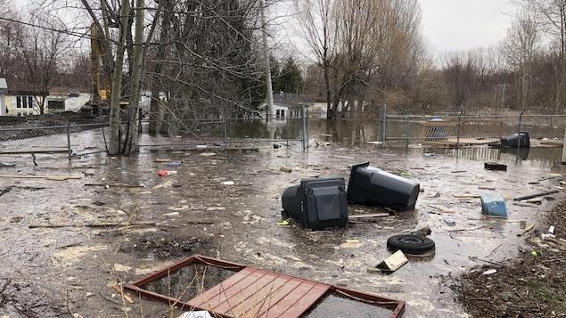 De nombreux débris jonchent une rue dans laquielle il reste un peu d'eau.