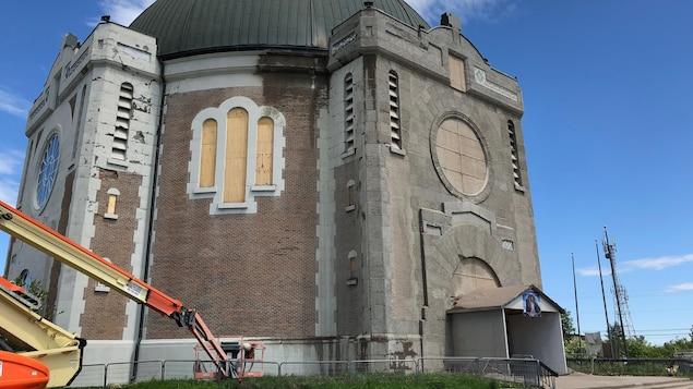 Une nacelle est stationnée devant la cathédrale d'Amos, dont des fenêtres sont barricadées.