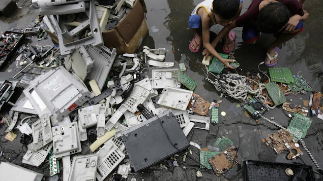 À Manille, des enfants recherchent des morceaux de cuivre parmi une pile de déchets électroniques.