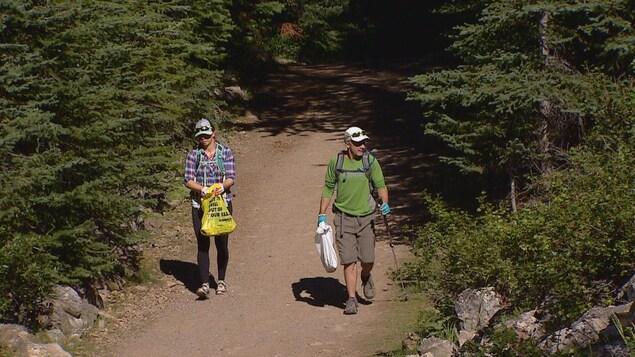 Deux randonneurs sur un sentier, chacun un sac poubelle à la main.