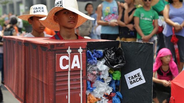 Un garçon déguisé en conteneur plein de déchets avec la mention «reprenez-les».