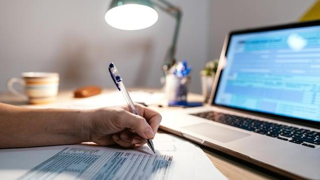 Une personne remplit sa déclaration de revenus sur papier.