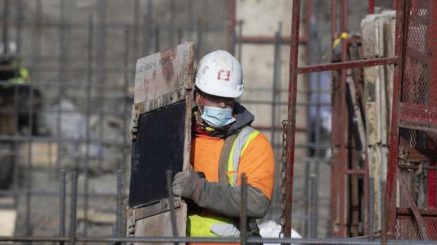 Un ouvrier portant un masque sur un chantier.