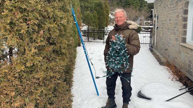 Un homme tient des lumières de Noël à l'extérieur de sa maison.