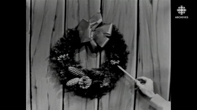 Une baguette pointe des petits fruits qui décorent une couronne de Noël.