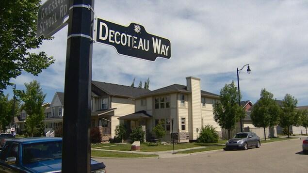 Panneau qui indique «Decoteau Way», ou rue Decoteau; en arrière-plan : des maisons, dans un quartier résidentiel d'Edmonton