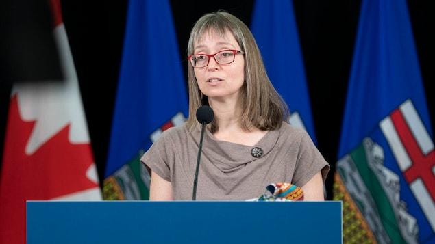 Deena Hinshaw, lors d'une conférence de presse, devant des drapeaux du Canada et de l'Alberta.