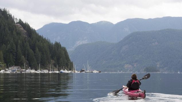 Une kayakiste s'avance sur l'eau avec en arrière-plan une marine située à la base de montagnes.
