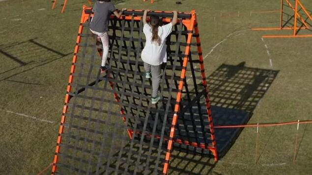 Deux jeunes filles montent un mur en filet.