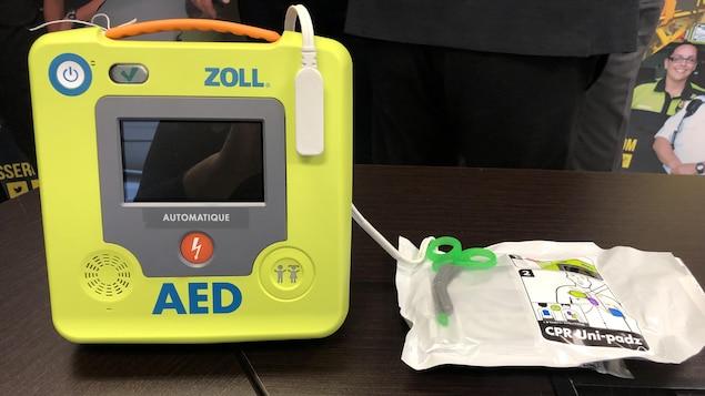 Un défibrillateur cardiaque automatique est posé sur une table.