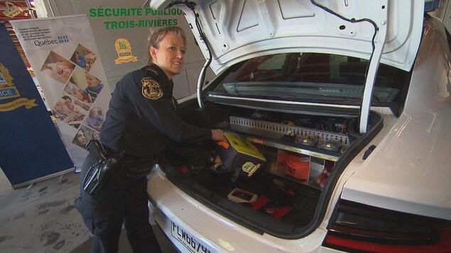 Une policière place un défibrillateur dans le coffre d'une auto-patrouille
