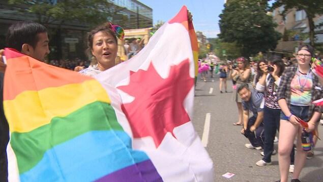 Une femme brandit le drapeau du Canada orné des couluers de la fierté gay