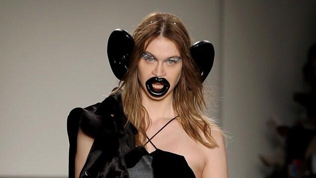 Une mannequin marche. Elle porte une robe noire ainsi que d'immenses lèvres et oreilles noires.