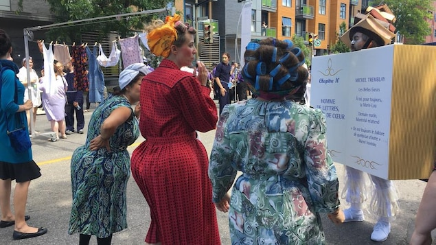 Des dames portant des robes d'antan et des boudins dans les cheveux marchent dans la rue.
