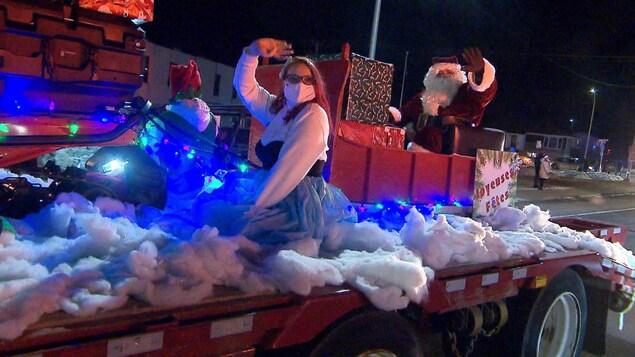 Le père Noël et la fée des étoiles dans un char allégorique.