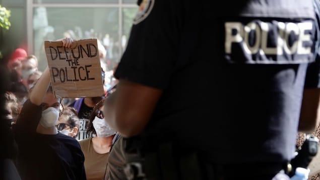 Une jeune femme brandit une pancarte où il est écrit « Defund the police » devant un officier torontois.