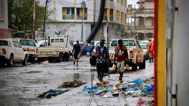 Deux personnes marchent sur le trottoir, jonché de débris.