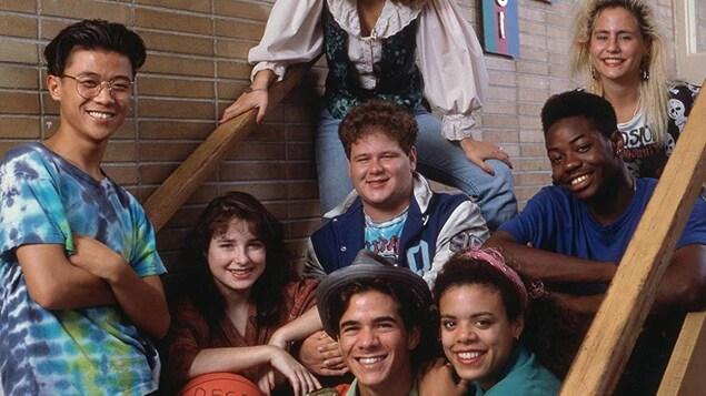 Les acteurs de la série Degrassi posent dans les marches d'un escalier dans une école.