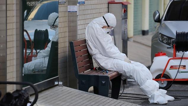Un travailleur médical en tenue de protection assis sur un banc