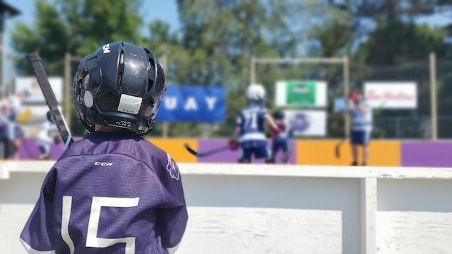 De jeunes enfants jouent au dek hockey dans un cours.