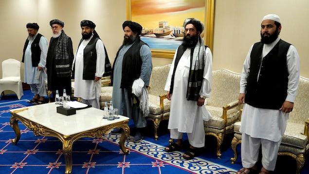 Six hommes afghans portant des tenues traditionnelles sont debout dans une salle de conférence.