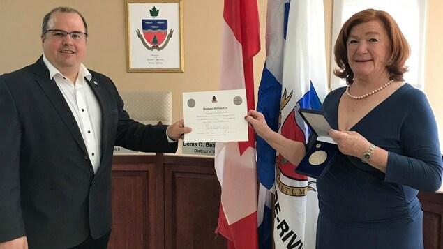 Délima Cyr tient une médaille et un diplôme à côté du maire Gino Cyr.