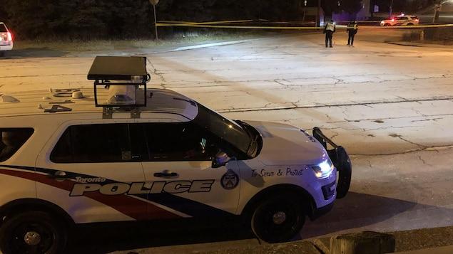 Photo d'un véhicule de police et d'une banderole jaune bloquant une rue. Deux policiers sont en arrière-plan.