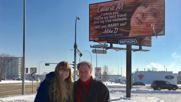 Un couple devant un panneau publicitaire dans un stationnement vide enneigé