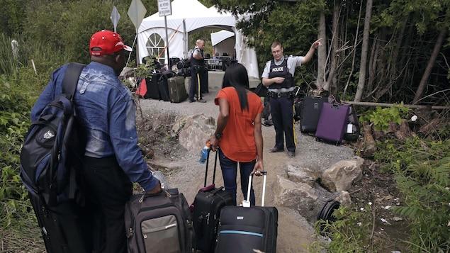 Un policier parle avec des migrants.