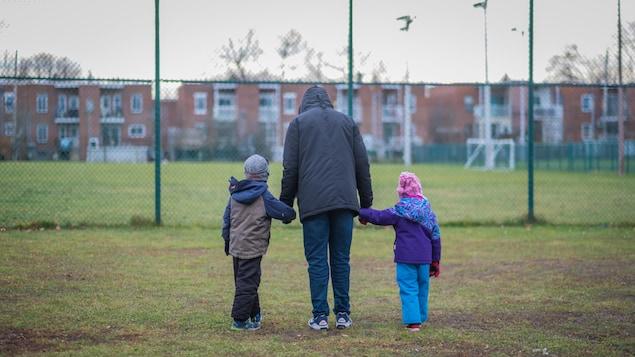Un homme tient un garçon et une fillette par la main. Tous sont de dos et marchent vers la clôture d'un terrain de soccer.
