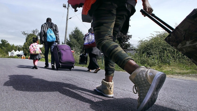 Des migrants haïtiens s'approchent de la frontière du Québec, transportant leurs valises.