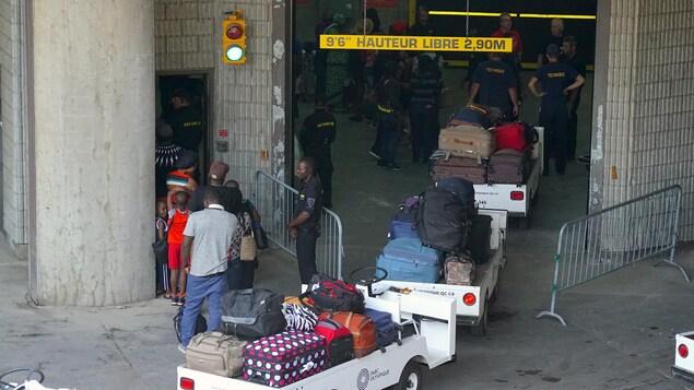 L'arrivée des demandeurs d'asile au stade olympique se déroule sous le regard de plusieurs agents de sécurité.