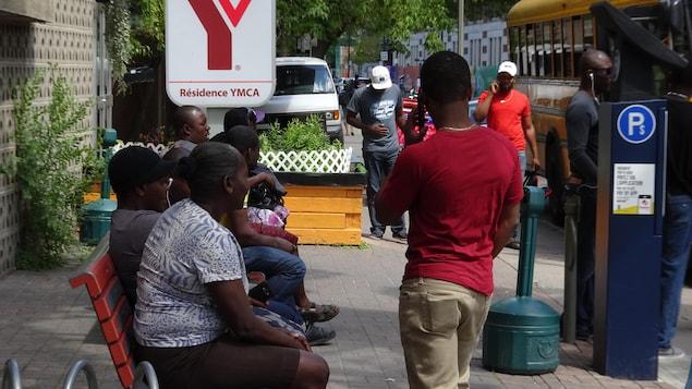 Des hommes, dont certains parlent au téléphone, devant l'enseigne du YMCA.