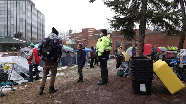 Un policier surveille des gens dans un campement de fortune.