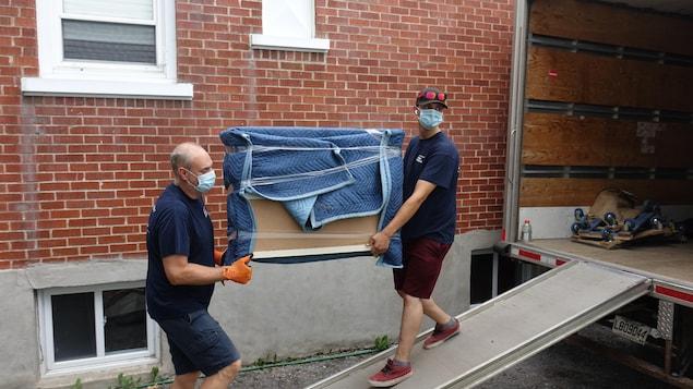 Des déménageurs portent un masque.