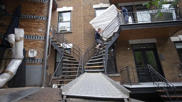 Deux déménageurs transportent un matelas dans des escaliers.