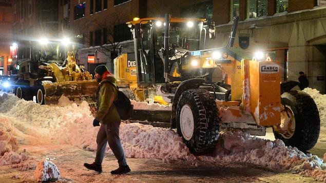 Un piéton traverse une rue enneigée alors que de la machinerie dégage la neige accumulée.