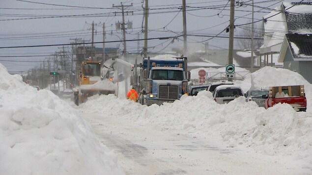 Une souffleuse souffle de la neige dans un camion dans une rue enneigée.