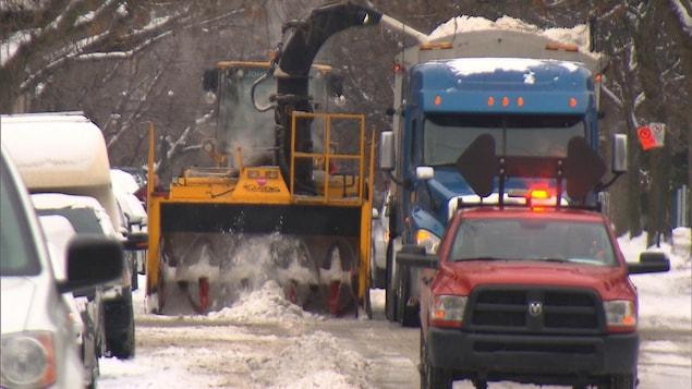Une souffleuse dépose la neige dans un camion.
