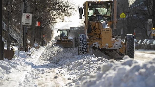 Des niveleuses poussent la neige en prévision de son chargement dans des camions.