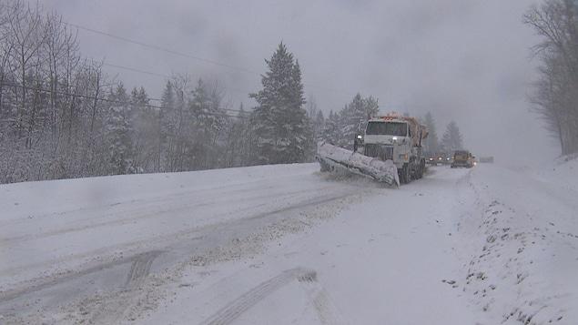 Un camion de déneigement circule sur la route 170 enneigée.