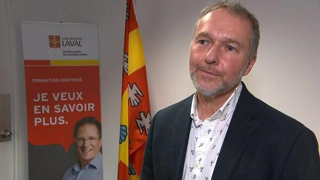 Denis Leclerc avec un complet foncé et une chemise blanche. Il est dans une petite salle avec des bannière de l'Université Laval derrière lui.