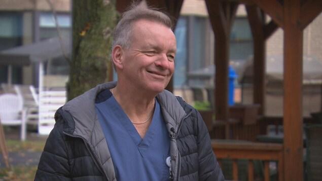 Un homme en uniforme de préposé aux bénéficiaires, sous son manteau, sourit devant le foyer où il travaille.