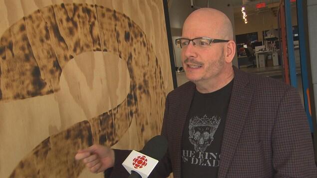 Denis Roy devant un micro de Radio-Canada.