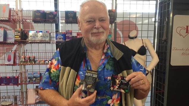 Un homme tenant dans ses mains des produits censés améliorer la performance sexuelle.