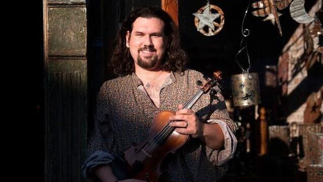 Le chanteur Dennis Stroughmatt avec un violon.